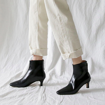 Black kitten heel boots against a white background